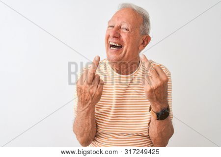 Senior grey-haired man wearing striped t-shirt standing over isolated white background Showing middle finger doing fuck you bad expression, provocation and rude attitude. Screaming excited poster