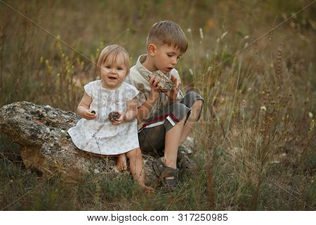 Two Small Children Brother And Sister Play Together. Happy Children Play And Smile In Nature. The Co
