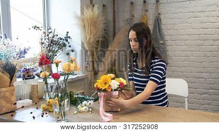 Female Florist In Flower Shop At Work.