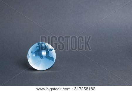 Blue Glass Planet Globe On A Gray Background. Globalization And Markets. Preservation Of The Environ