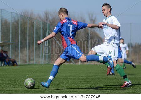 KAPOSVAR, HUNGARY - MARCH 17: Marton Lorentz (blue) in action at the Hungarian National Championship under 18 game between Kaposvar (white) and Videoton (blue), March 17, 2012 in Kaposvar, Hungary.