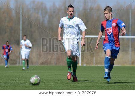 KAPOSVAR, HUNGARY - MARCH 17: Daniel Vaszilko (white) in action at the Hungarian National Championship under 18 game between Kaposvar (white) and Videoton (blue),  March 17, 2012 in Kaposvar, Hungary.