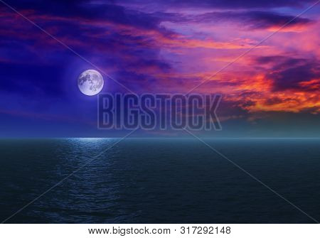 Fantastic Red Skies And A Big Moon Over The Blue Sea At Night.