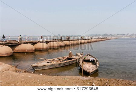 Varanasi, India: Boatman Waiting For Passengers In Riverboat Near The Pantone Bridge Across The Wide