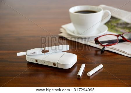 Rieps, Germany, August 15, 2019: Iqos Heating Tobacco System, Coffee Cup And Newspaper On A Brown Ta