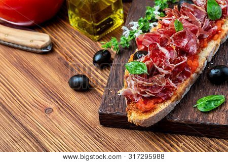 Delicious Bread Toast With Natural Tomato, Extra Olive Oil, Iberian Ham, Black Olives And Basil Leav