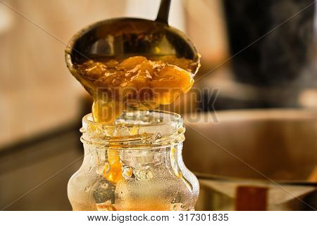 Pouring Prepared Homemade Peach Marmalade In Glass By Mettal Ladle In Kitchen