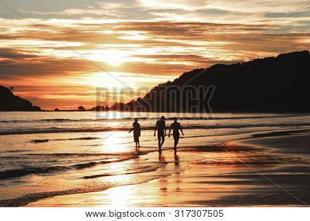Friends walking on the beach at sunset