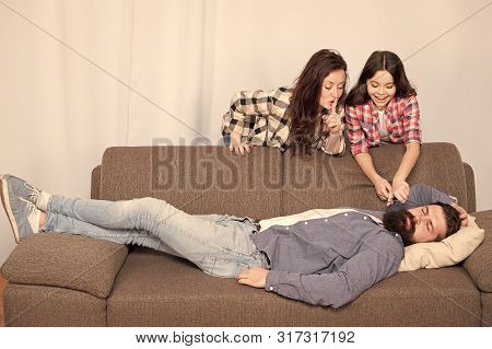 Family Prank. Little Girl With Mother Cut Fathers Beard. Happy Family At Home. Bearded Man Relax On