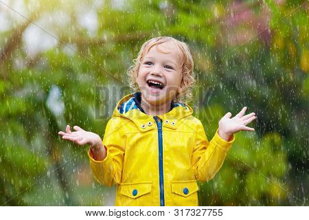 Kids Play In Autumn Rain. Child On Rainy Day.