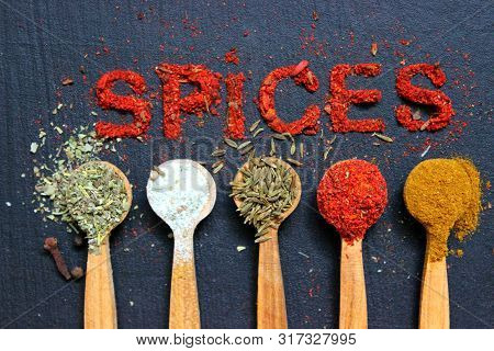 The Word Spice Is Written On A Black Background. Various Spices Ground Turmeric Pepper Ginger Cinnam