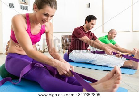 Group of people doing foot exercises with thera band in yoga class