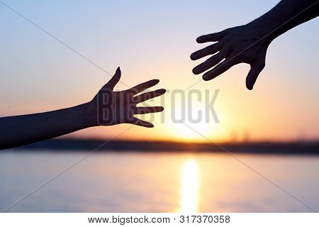 Giving A Helping Hand. Silhouette Two Hands, Man And Woman, Reaching Towards Each Other At Sky Sunse