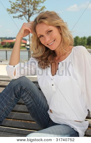 Blond woman relaxing on park bench