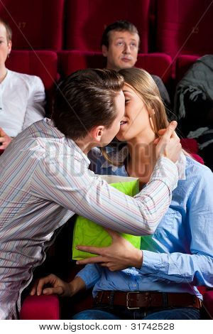Couple in cinema watching a movie, they eating popcorn and kissing