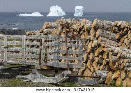 Old Traditional Wood Sled, Stack Of Firewood, Iceberg Along Newfoundland Seacoast