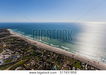 Aerial view of large pacific ocean view homes and Zuma Beach in Malibu California.