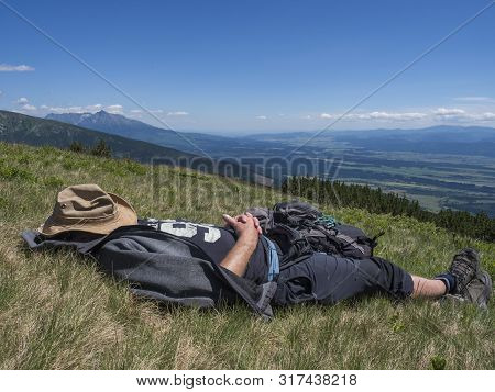 Man Hiker In Hat Taking A Nap At Meadow With Mountain Landscape Of Western Tatra Mountains Or Rohace