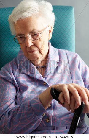 Unhappy Senior Woman Sitting In Chair Holding Walking Stick