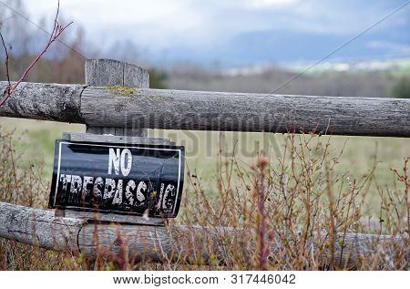 No Trespassing Sign On Old Wooden Fence With Tall Weeds