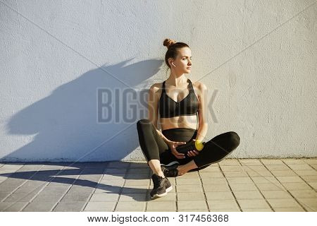 Fitness Sporty Woman With Headphones Relaxing After Workout. Beautiful Fit Girl In Black Sport Wear.