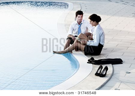 Two young people working free with feet in the pool