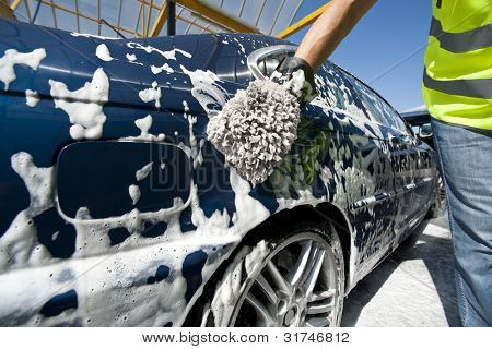 Close-up of a man cleaning his car using a sponge