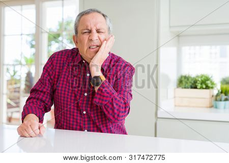 Handsome senior man at home touching mouth with hand with painful expression because of toothache or dental illness on teeth. Dentist concept.
