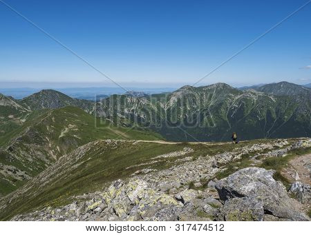 Mountain Landscape Of Western Tatra Mountains With Woman With Bacpack And Dog On Hiking Trail On Bar