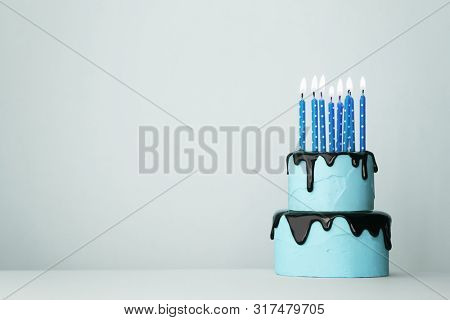 Blue tiered birthday cake with eight candles