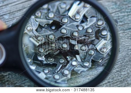 Black Magnifier Enlarges The Gray Steel Chain Saw On The Table