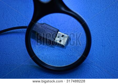 Magnifier Enlarges Black Usb Cord With Plug On Blue Table