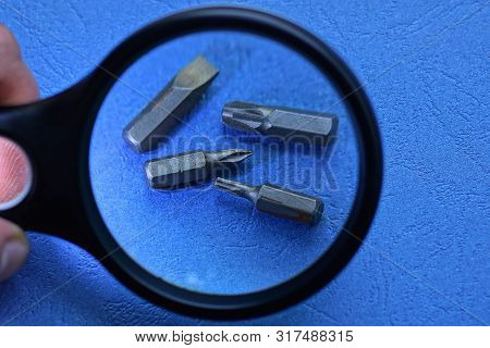 Black Magnifier Increases The Set Of Metal Bits Of A Screwdriver On A Blue Table