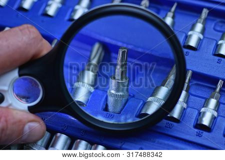 Black Magnifier Enlarges Screwdriver Bit In Blue Plastic Box