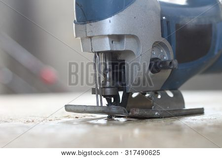 Blue-silver Electric Jigsaw On The Osb Plate. The Process Of Sawing Osb Plywood