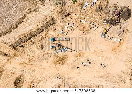 Group Of Industrial Machines Installing Water Drainage System At Construction Site. Drone Image