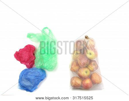 Reusable Recycled Mesh Net Grocery Bag Full Of Apples And Heap Of Colored Disposable Plastic Bags, O