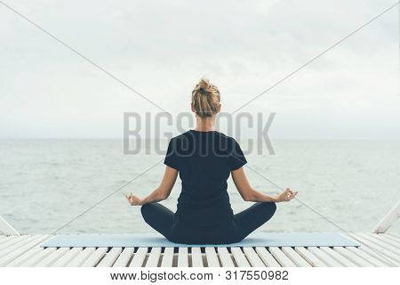 A Young Woman In A Yoga Asana With Her Back To The Camera Meditates While Looking At The Sea Waves.