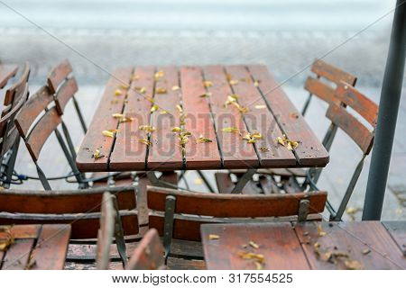 End Of Season, Unused Outdoor Folding Set Of Wood And Metal From A Street Restaurant In Autumn With