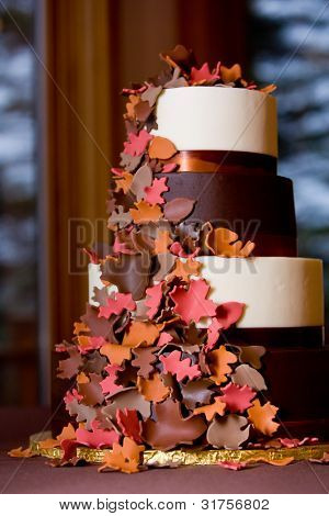 A Fancy fall themed wedding cake with sugar leaves falling down the side