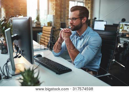 Thinking. Side View Of Young Bearded Man In Eyeglasses And Formal Wear Working On Computer And Keepi