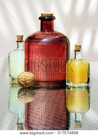 Still Life With Whole Walnut And Three Vintage Glass Bottles With Lemon, Orange And Grape Juice Agai