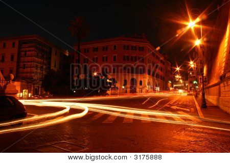 A timed exposure of traffic at night in the city of Rome Italy by photgrapher Dan Manning. poster