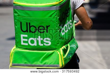 Bucharest, Romania - August 13, 2019: An Uber Eats Food Delivery Courier Delivers Food In Bucharest,