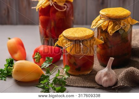 Homemade Jars Of Pickled Peppers And Tomatoes On A Rustic Wooden Background. Pickled And Canned Prod