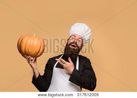 Vegetarian Pumpkin For Diet Salad. Carving Big Orange Pumpkins For Halloween. Bearded Man In Chef Ha