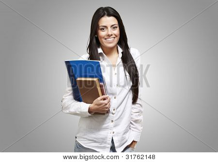 young student holding books and smiling against a grey background