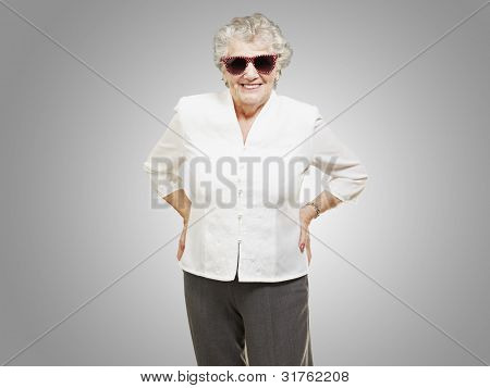 portrait of a happy senior woman against a grey background