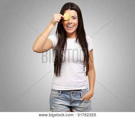 portrait of a young woman holding a potato chip in front of her eye over a grey background