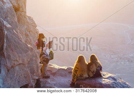 Sinai Peninsula, Egypt, May 9, 2019. Girls Greet Dawn And Take Pictures On Mount Moses, Sinai Penins